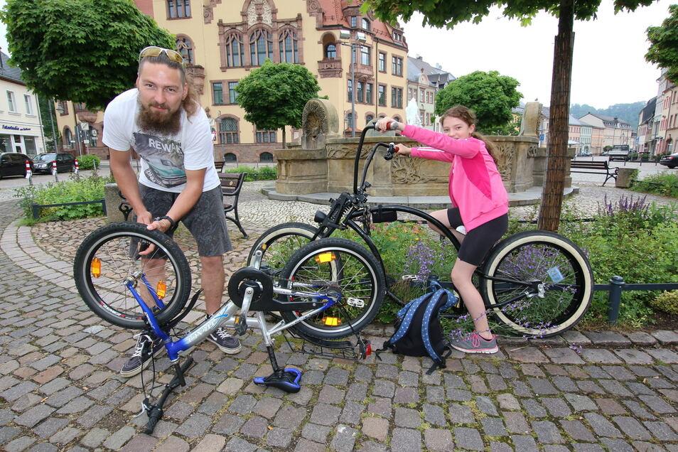Martin Hahn pumpt noch mal Luft auf dem Rad seiner Tochter Cora auf. Die darf derweil auf der Tret-Harley Platz nehmen, mit der ihr Vater dann unterwegs sein wird.