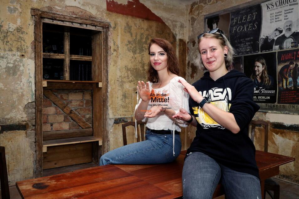 """Vanessa Sprößig genannt Conrad (l.) und Klara Schlichting zeigen die Plakette von """"Ab in die Mitte"""". Der Wettbewerb hatte die Finanzierung für den Jugendladen weitgehend gesichert."""
