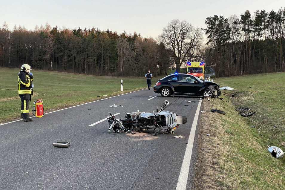 Das Motorrad liegt schwer beschädigt auf der Straße, einige Meter entfernt steht der an der Front zerstörte VW Beetle.