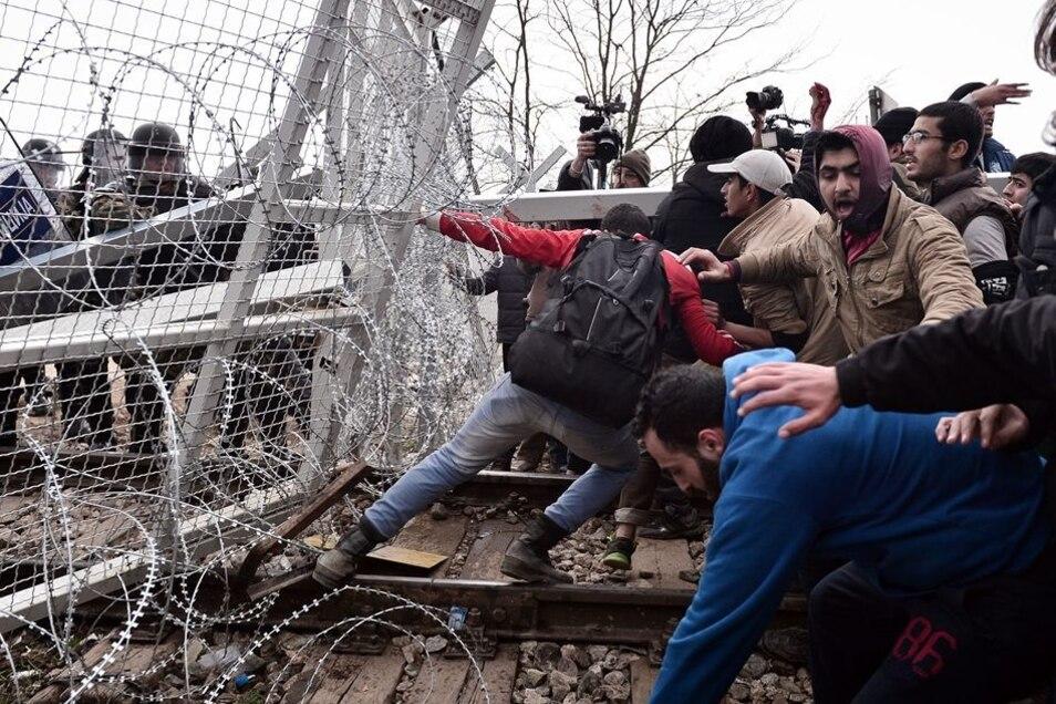 Flüchtlinge zerren am Grenzzaun zu Mazedonien.