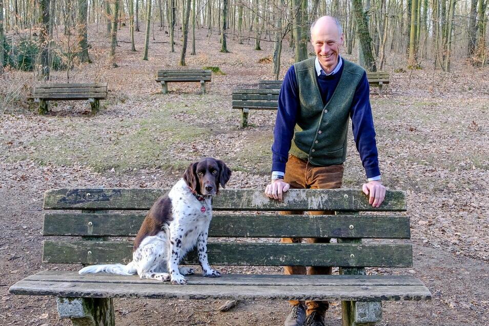 Stadtrat Hans Kraske (Freie Wähler) steht an einer Bank der Naturbühne bei Schwarzes Teich, auf der sein Hund Platz genommen hat. An den Sitzgelegenheiten nagt unübersehbar der Zahn der Zeit.
