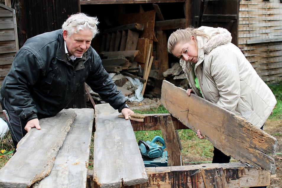 Edelbert Niedan (Zimmerer) und Cornelia Schnippa (Vorsitzende des Fördervereins HeimatHOF Lieske) sichten Stücke des originalen Holzes: Was ist wiederverwendbar – und was wird auf Grund zu starker Abnutzung durch neue Bauelemente ersetzt werden müsse
