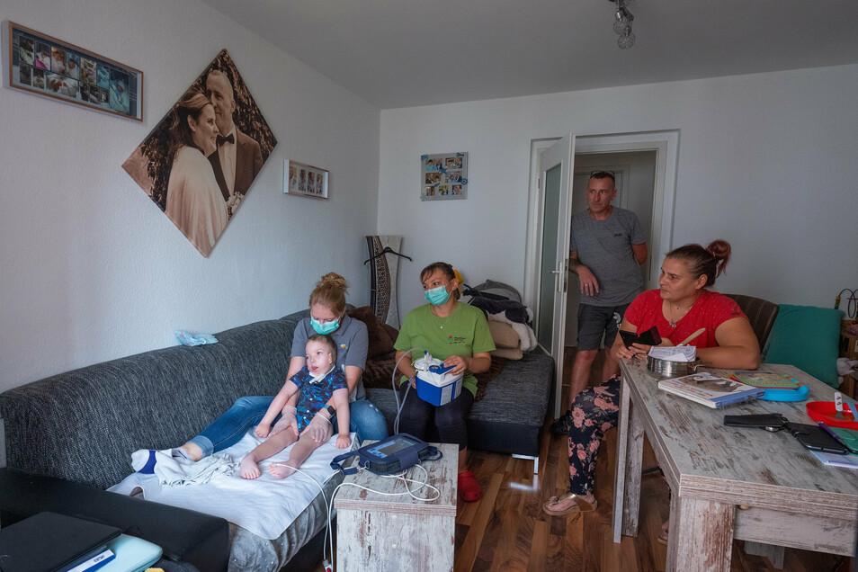 Silke Hunger und Ehemann Carsten, Pflegerin Franziska Hauschild, Physiotherapeutin Mandy Borgwardt und Leon (v. r.) im Wohnzimmer der 56-Quadratmeter-Wohnung.