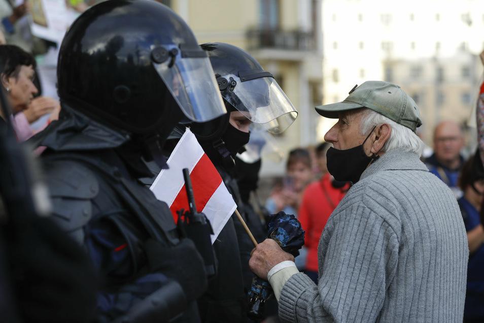 Ein älterer Demonstrant spricht mit einem Polizisten während der Demonstration in Minsk.