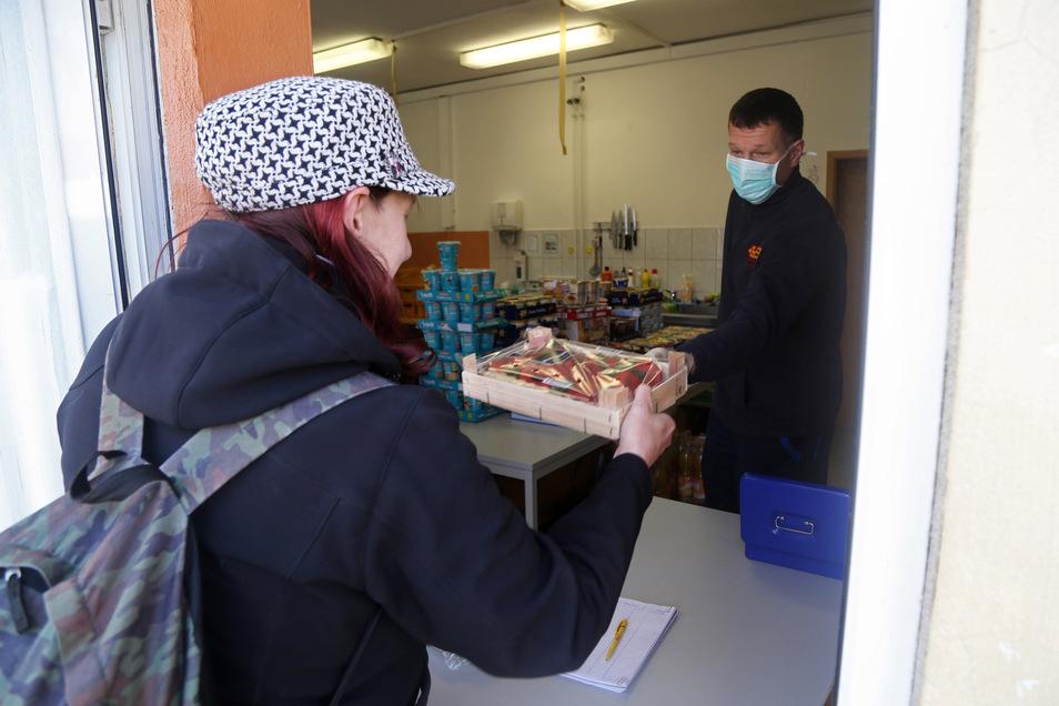 Tafel-Leiter Sten Kunert reicht Kerstin Mittelstädt eine Stiege Obst.