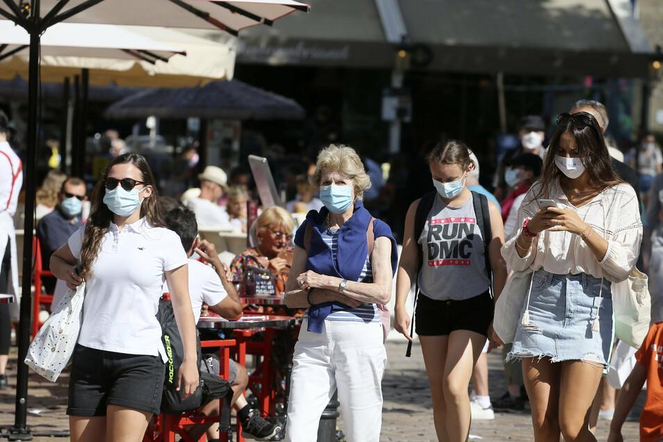 Touristen in Frankreich tragen Mundschutz-Masken, während sie die Stadt besuchen. Am 2. August trat eine Maskenpflicht im Freien in Kraft. In Deutschland sind Masken nur in Geschäften und öffentlichen Innenräume nötig.