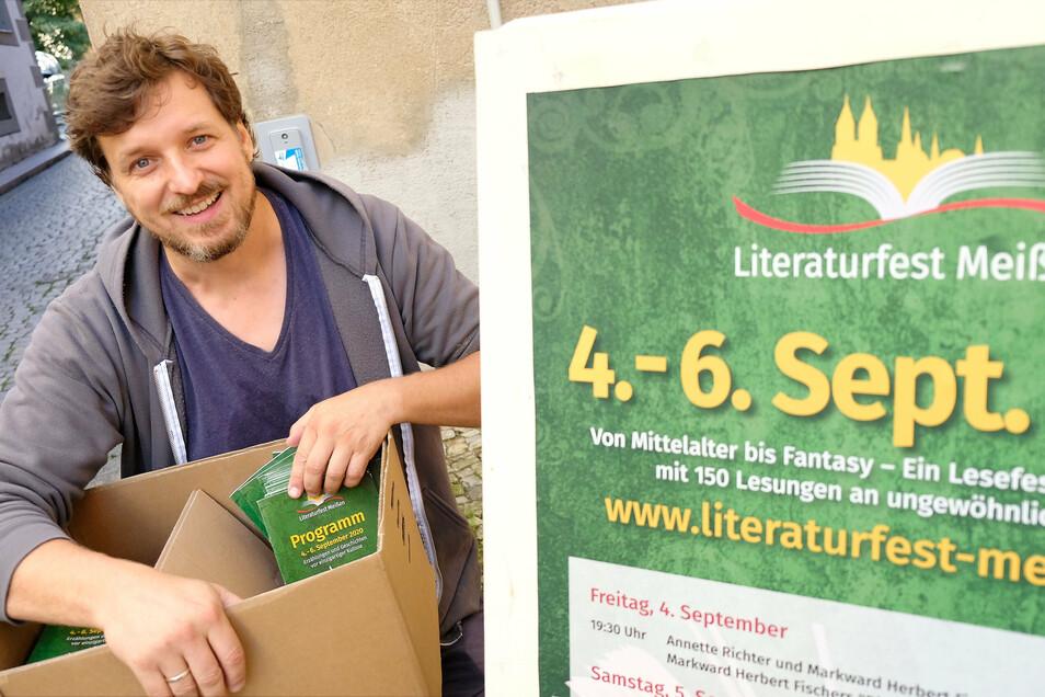 Daniel Bahrmann, der dem Organisatorenteam des Meißner Literaturfestes vorsteht, verteilt die druckfrischen Programmhefte.