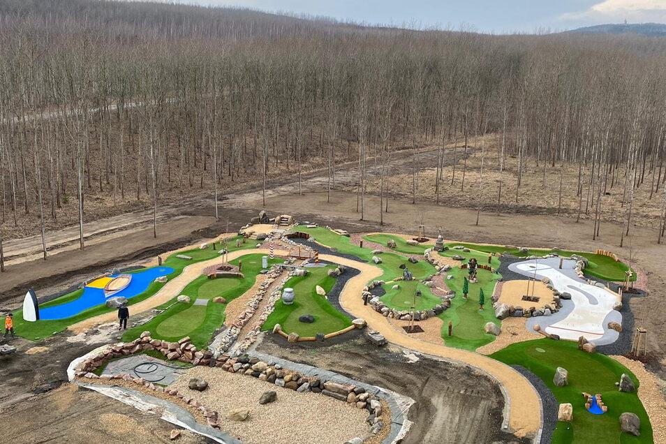 Ein Blick auf die gesamte Anlage vom Hochseilgarten aus: Erkennbar ist der Berzdorfer See, der hier - wie viele andere Markenzeichen der Grenzregion - nachgebaut wurde. 34 Adventure-Golfplätze hat das Unternehmen bislang in sechs Jahren gebaut - und allein in diesem Jahr kommen zwölf weitere hinzu.