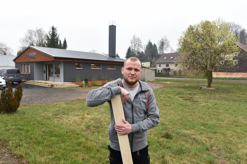 David Schmieder steht hier vor seiner Tischlerei in Reichstädt. Auf der Wiese hinter ihm will er eine neue Halle anbauen.