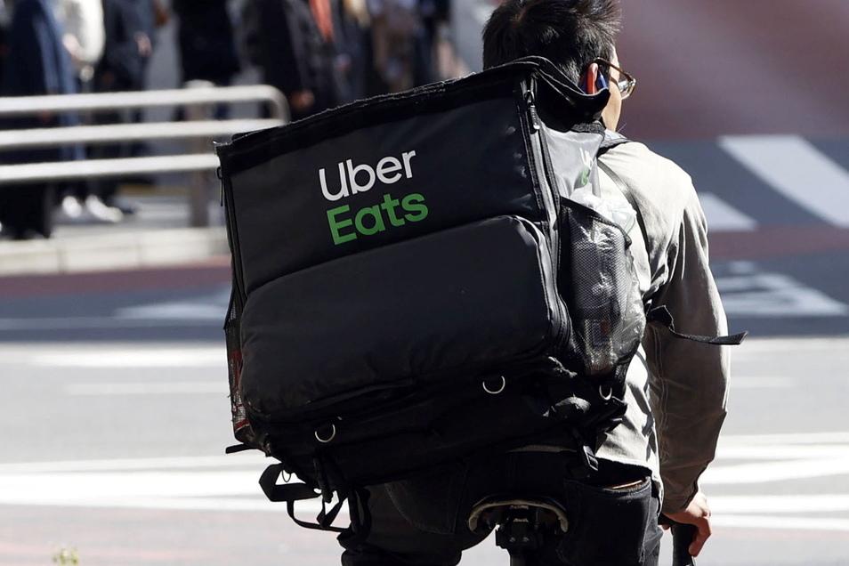 Neben den orange gekleideten Lieferando-Auslieferern sollen künftig auch schwarz gekleidete Uber-Fahrer in Deutschland Essen nach Hause bringen.