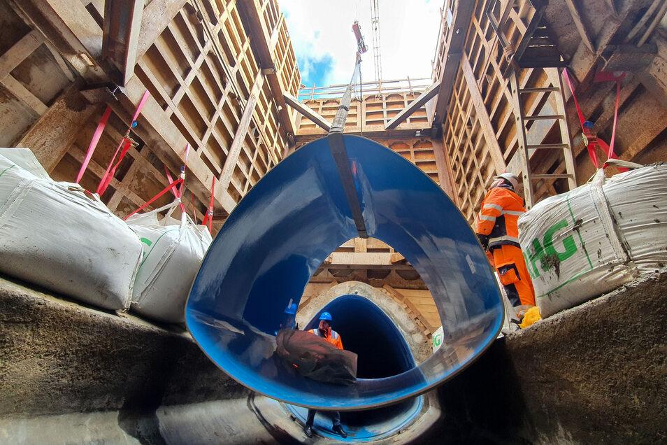Hier wird ein zwei Tonnen schweres Kunststoffteil in die tiefe Baugrube gehoben. Mittlerweile sind alle derartigen Teile in den alten Kanal eingebaut.