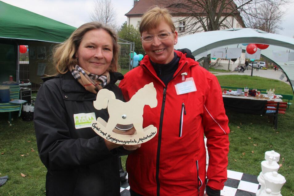 """Diana Voß (l.) und Anja Kloß von der Initiativgruppe für einen Spiel- und Begegnungsplatz zeigen das """"Sammelpferdchen"""" für die Finanzierung des Projektes."""