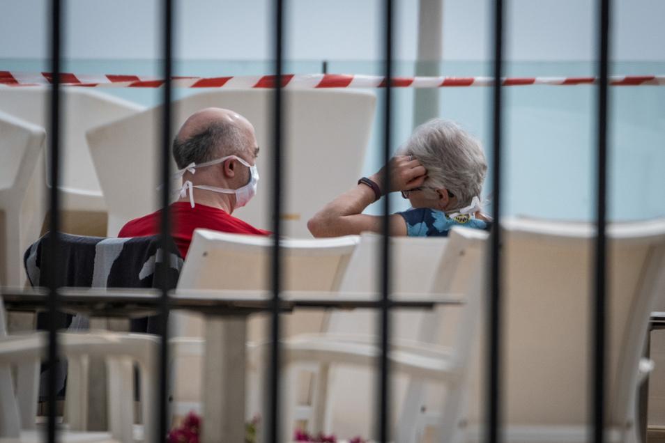 Ein Paar sitzt mit Mundschutz am Swimmingpool des Hotels H10 Costa Adeje Palace in Teneriffa. Das Hotel wurde wegen Coronavirus-Fällen unter Quarantäne gestellt.