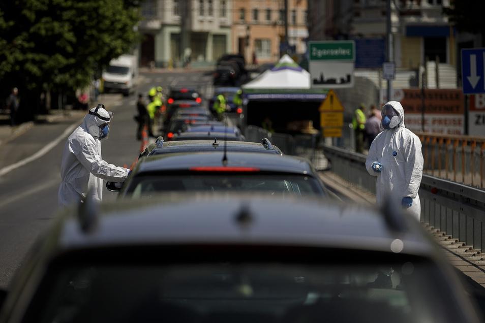 In Schutzanzügen kontrollieren die Polen alle, die über die Grenze wollen. Auch Fiebermessen gehört zum Repertoire.