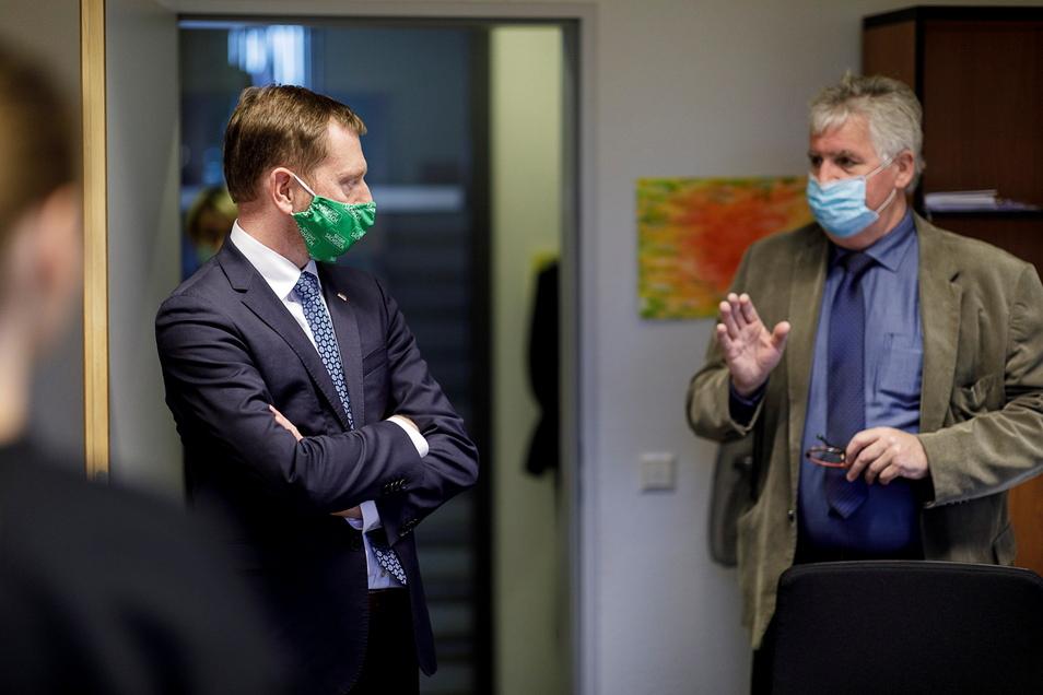 Ministerpräsident Michael Kretschmer kann sich warm anziehen: Der Landkreis (rechts Landrat Bernd Lange) droht mit Klage.