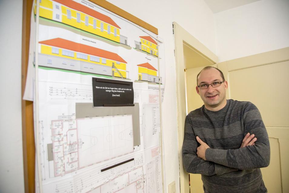 Dirk Naumburger ist Bürgermeister von Kreba-Neudorf und will es auch bleiben. An der Wand hängen die Pläne für den Neubau der Sporthalle. Inzwischen ist sie baulich fertiggestellt.