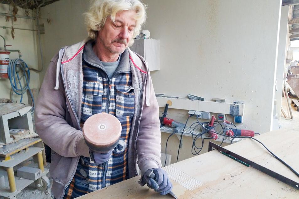Uwe Hoppe und seine Steinmetzkollegen bearbeiten derzeit in den Pirnaer Sandsteinwerken Teile für die Augustusbrücke. Hier ist er mit Knüpfel und Scharriereisen an einem Konsolstein aktiv.