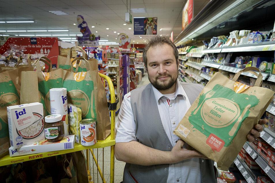 Rewe-Marktleiter Benjamin Geschwill zeigt eine Tüte, wie sie von Kunden des Marktes erworben werden können.