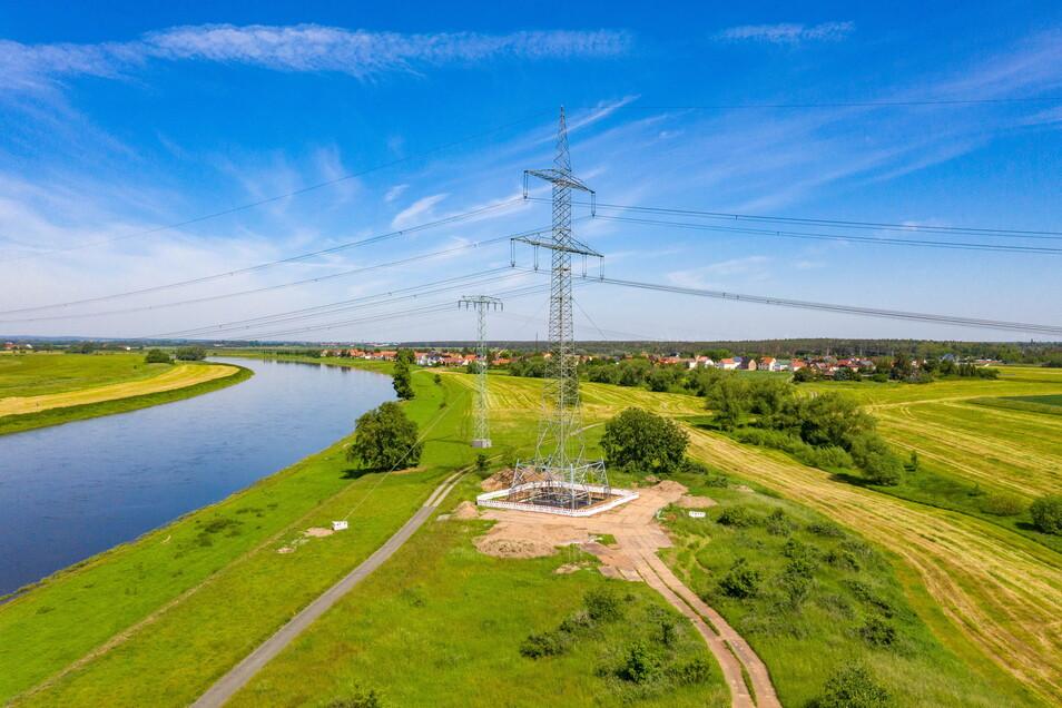 Am Fuß des alten Hochspannungsmastes wächst nun ein neuer - deutlich größer. Links ist die Elbe zu sehen, im Hintergrund der Zeithainer Ortsteil Gohlis.
