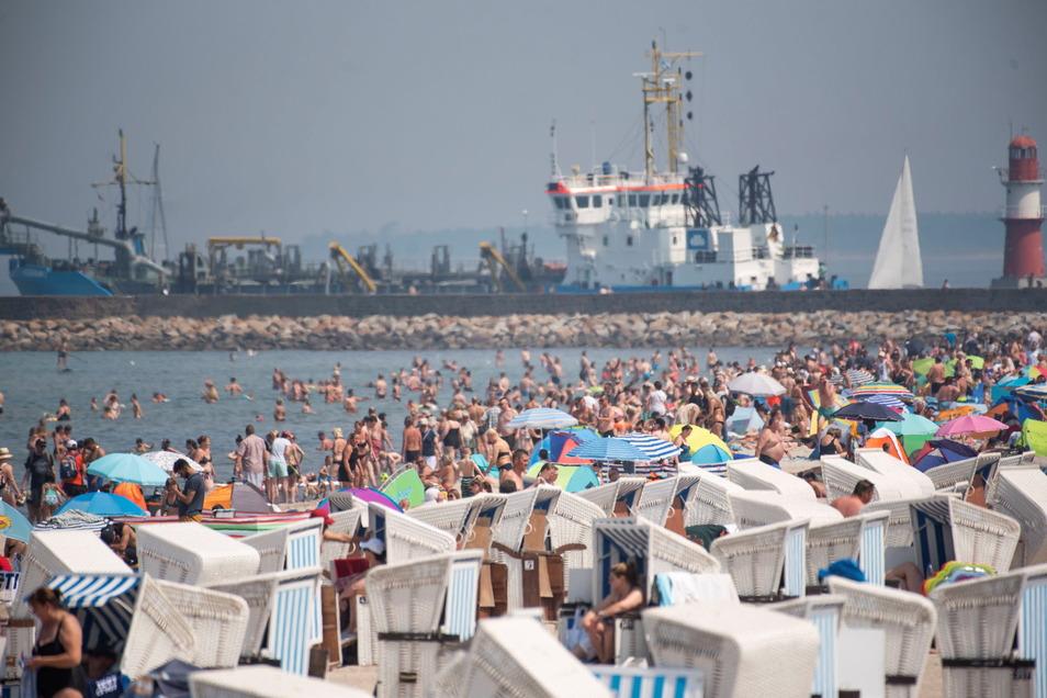Urlauber in Rostock halten sich bei hochsommerlichem Sonnenwetter am Strand auf.