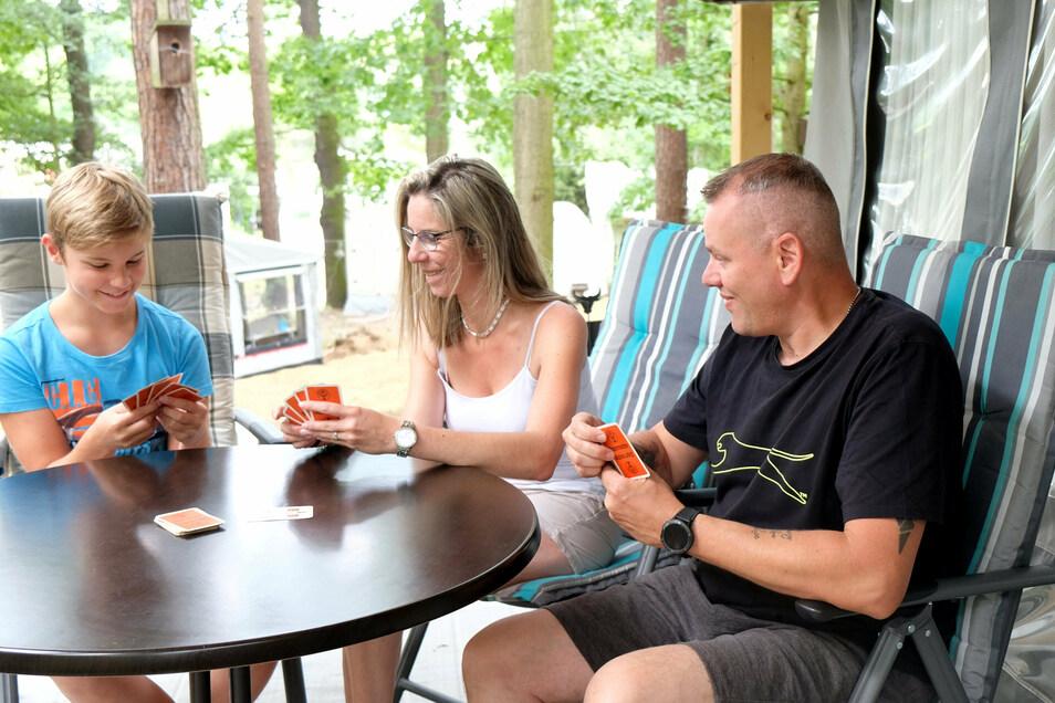 Lias und Claudia Behrend spielen gemeinsam mit Tobias Siegel Karten auf dem Campingplatz in Oberau, wo die kleine Familie ihren diesjährigen Urlaub verbringt.