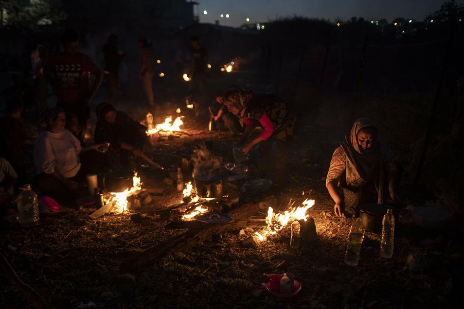 Migranten kochen auf behelfsmäßigen Feuern in der Nähe einer verlassenen Fabrik auf der griechischen Insel Lesbos, nachdem das Lager Moria abgebrannt ist.