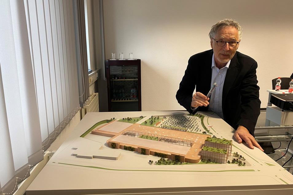 Kurt Krieger zeigt das Modell des neuen Einkaufszentrums, auf dessen Dächern geparkt werden soll.