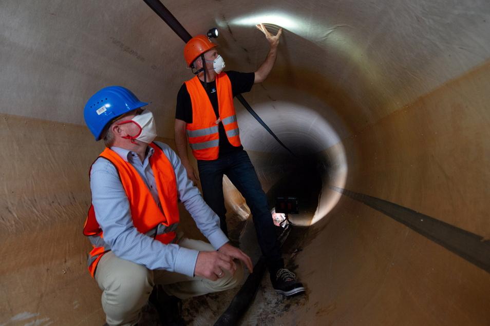 Ein Blick in die große Abwasserröhre unter dem Elbgrund gleich nach der Sanierung im April 2020. Damals prüften der Chef der Stadtentwässerung Ralf Strothteicher (l.) und Bauleiter Martin Lehmann die neue Kunststoffhülle, die den Tunnel sicher abdichtet.