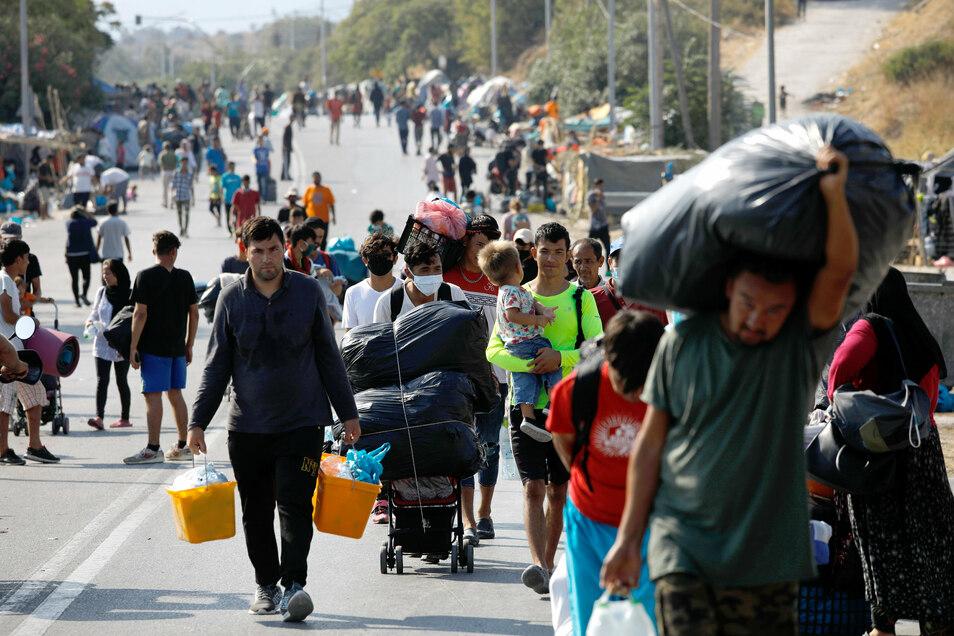 Migranten tragen ihre Habseligkeiten vom abgebrannten Flüchtlingslager Moria in einen anderen Ort. Der Landkreis Bautzen solle mindestens zehn minderjährige Flüchtlinge aufnehmen, fordern die Grünen im Kreistag.