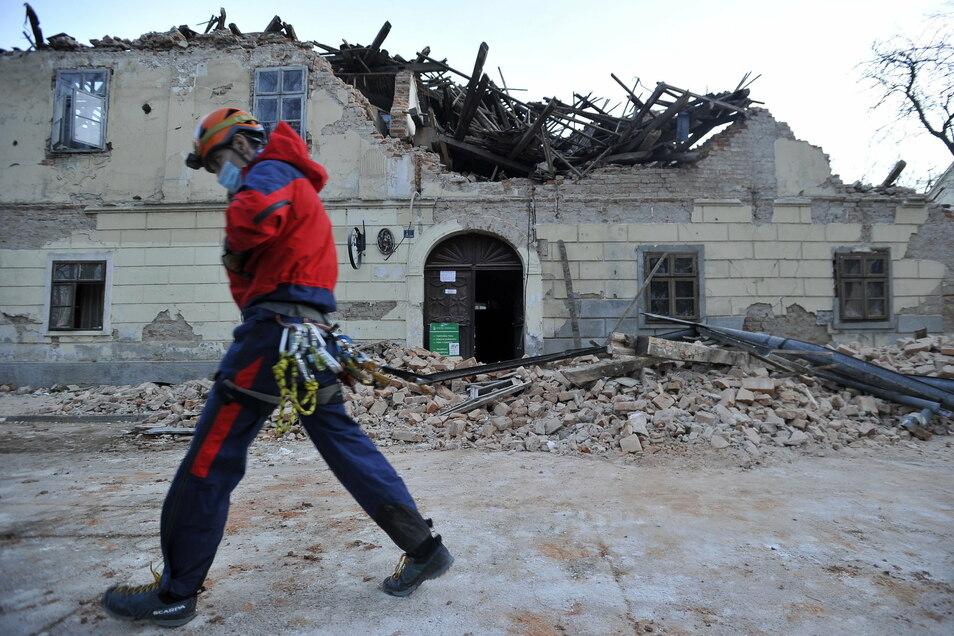 Kroatien, Petrinja: Ein Mitglied der Rettungskräfte geht vor den Trümmern eines eingestürzten Hauses vorbei.